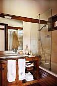 Badezimmer mit Waschtisch-Unterschrank, daneben Badewanne mit Glasabtrennung