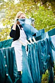 Woman hanging out hand-died blue textiles to dry on washing lines in garden