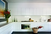 White, modern fitted kitchen with counter running along two walls