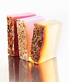 Hand Crafted Natural Soaps on a Reflective Surface; Rose, Lavender and Rosemary Mint