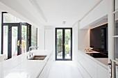 Minimalistische, weisse Kücheninsel auf dunkel gerahmte Terrassentüren