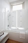 Duschbadewanne und Glasabtrennung vor Altbaufenster mit innenliegenden Klappläden