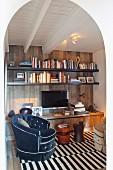 Blick durch Rundbogen auf Raum mit weisser Holzbalkendecke und brauner, holzverkleideter Wand; im Vordergrund ein anthrazitfarbener Samtsessel auf braun-weiss gestreiftem Teppich
