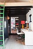 Weisser Schreibtisch mit weißem Eames-Drehstuhl unter dunkler Holzbalkendecke; im Vordergrund eine grüne Vintage-Leiter