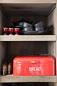 Pans, crockery and red bread bin with lettering on kitchen shelves