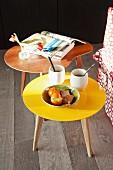 Zwei Couchtische im Retro-Look mit Bücherstapel, Teebecher, Blumenvase und Obstschale