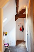 Bright, child's bedroom with rustic roof beams and desk below skylight; colourful Hang-it-all coat rack in background
