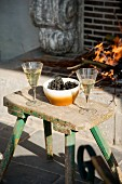 Glasses of white wine and grapes on vintage stool used as side table in front of open fire