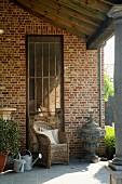 Wicker chair in front of old rusty metal door on veranda with column