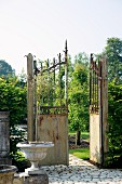 Rustic iron gate leading to well-tended garden with trees and paved path