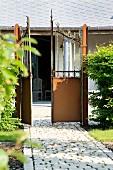 Offenes Gartentor mit Blick zum Wohnhaus mit Veranda