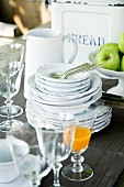 Stack of white crockery, glasses and fruit bowl on brown linen tablecloth