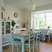 Cosy, cottage-style kitchen-dining room with old dining table painted pastel blue and wicker sofa with colourful patchwork blanket