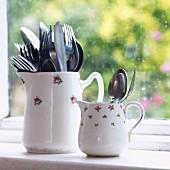 Grosses und kleines Besteck in zwei alten Porzellankannen mit Blümchenmuster vor einem Fenster