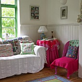 Patchwork and floral patterned blankets and cushions in corner of interior with half-height wood panelling
