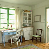 Interior in pastel shades with half-height wooden panelling, glass-fronted dresser and small table with drawers below window with green-painted frame