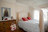 Country-house-style bedroom with old chest of drawers and draped mosquito net over double bed