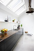 Monolithic kitchen counter with black fronts below strip of skylights and metal, industrial-style pendant lamps