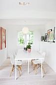 Moderner, weisser Küchentisch und Schalenstühle aus Bauhauszeit im Esszimmer