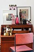 Eklektische Vintage-Dekoration auf Sekretär kombiniert mit samtigem 70er Jahre Polsterstuhl