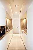 Futuristic designer kitchen - narrow room with white and pale grey installations on both sides and suspended ceiling with recessed spotlights