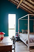 Rustic child's bed with four-poster frame, turquoise wall, table and chair in attic room