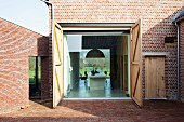 Open, barn-style doors - view from courtyard of brick housing complex into modern dining room
