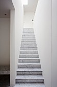 Narrow stairway with marble steps and view of stone bench through open doorway to one side