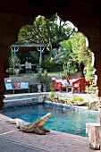 View of crocodile statue on side of pool through carved wooden archway
