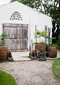 Buddha und Tierfiguren um Pflanzkübel vor schlichtem Haus mit verwittertem Holztor