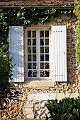 Lattice window with white wooden shutters in climber-covered stone facade