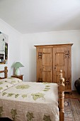 Rustic bedroom - double bed with carved wooden frame and wooden wardrobe with metal fittings