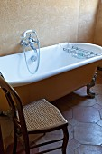 Chair with cane seat next to vintage bathtub in rustic bathroom