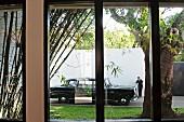 Blick aus dem Fenster auf eine schwarze Oldtimer- Limousine mit schwarzgekleideter Person vor weißer hoher Wand