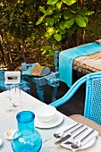 Place setting with cutlery on table and blue outdoor chair on garden terrace