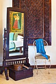 Wood-framed cheval glass and vintage metal chair in front of carved panel in corner of room