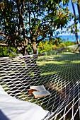 Open book on hammock hung between green trees below blue sky