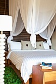 Green rug beside double bed below white canopy against dark wooden wall