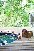 Wooden terrace with round pool, basket of rolled towels and champagne bucket against backdrop of green trees