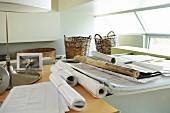 Papierrollen und Pläne auf Schreibtisch im Büro