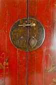 Metal shield with red tie on wooden cabinet in Asian style