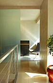 Hallway with modern metal stair railing and looking through an open doorway on swivel chair