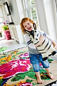 Laughing child with toy animal on colourful kilim rug