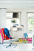 Colourful towel on swivel chair and white, modern dining area with bright kilim rug in background
