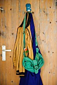 Crumpled bag and clothing hanging from metal hook on stripped, vintage door