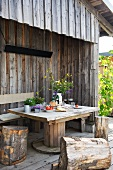 Table with bench and tree stump stools on terrace of wooden cabin