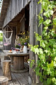 Flowers on wooden table and tree stump stools on terrace of wooden cabin