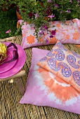 Batik-patterned and Paisley-print cushions on bamboo mat in summer garden