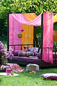 Exotic colour composition in garden - modern metal couch with patterned cushions and airy fabric canopy