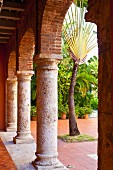 Peaceful arcade with rounded arches and view into courtyard with lush foliage